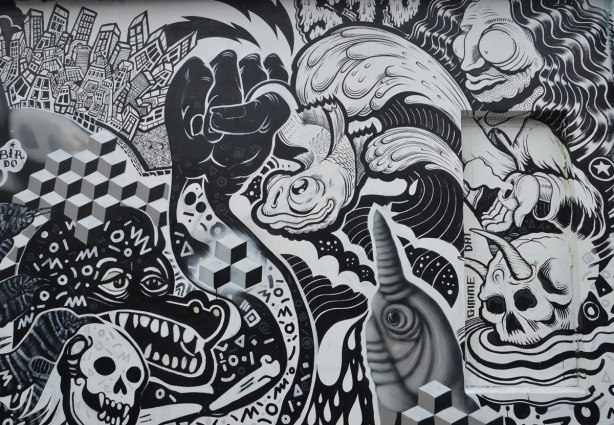 detail of a black and white mural by birdo and en masse with sybols of death and decay.