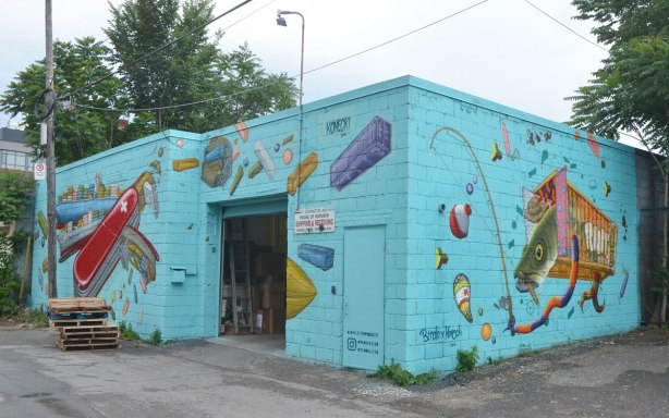 mural on two sides of a building in an alley, on turquoise, large swiss army knife, and a fish in a cage, reaching out with a long skinny arm, with a fishing rod
