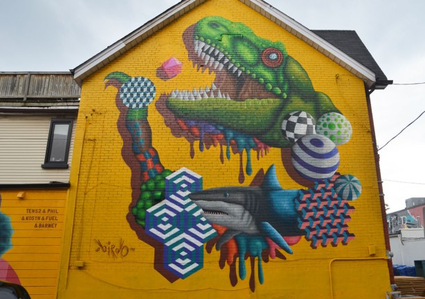 large mural by birdo, street art, on a two storey bright yellow building, a shark, and an alligator (or crocdile) head