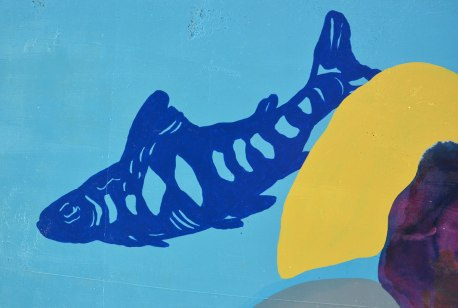 street art painting of a blue fish on light blue background, stylized