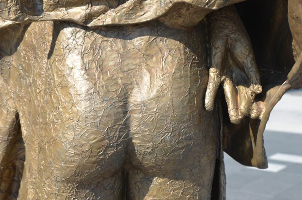 part of a bronze sculptture, a naked bum with a hand beside it.