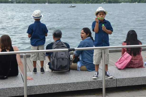 A family sits by the lake, two young sons in matching fedoras. Mother is yawning, father and one son have backs to camera, other son is blowing bubbles towards the camera