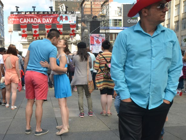 A man in a red cowboy hat in the foreground on the right, a couple kissing on the left. People watching a show on a stage in the background with Canadian flags and a banner that says Happy Canada Day