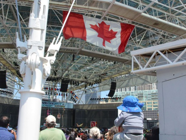Canadian flag flying high at harbourfront, over the heads of people in a crowd