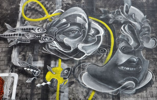 Close up of the top half of a mural by caratoes in grey tones, fish and faces