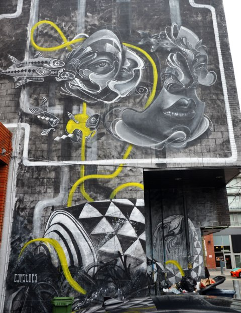 a two storey vertical mural by caratoes in grey tones, fish and faces on the top and an object made of black and white triangles on the bottom