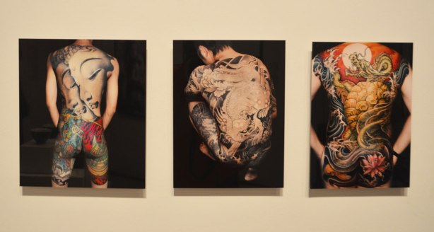 Three pictures of the backsides of men, each with a large picture tattoo from neck to thigh. Chinese art pictures as tattoos
