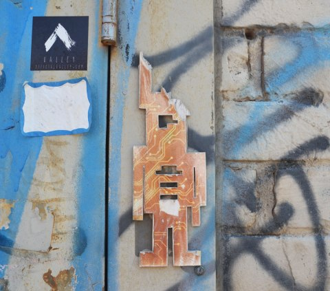 a little stikman covered with circuit board symbols, missing part of his head, on a door frame outside,