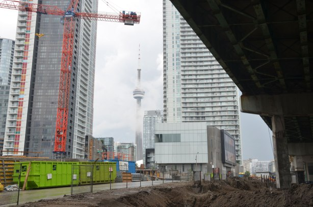 construction site under the Gardiner, cranes and condos being developed on the left, CN tower in the fog in the distance.