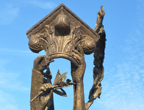 part of a public art installation outdoors created by piecing together fragments of other statues cast in bronze, hands, top of a column and a laurel leaf