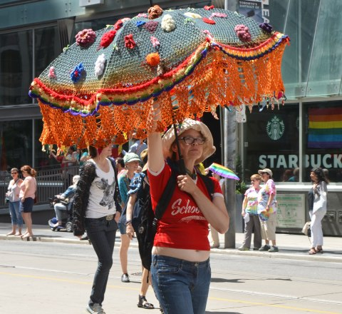 walkers in a dyke march in Toronto - a woman carries a large crocheted umbrella with a multicoloured fringe