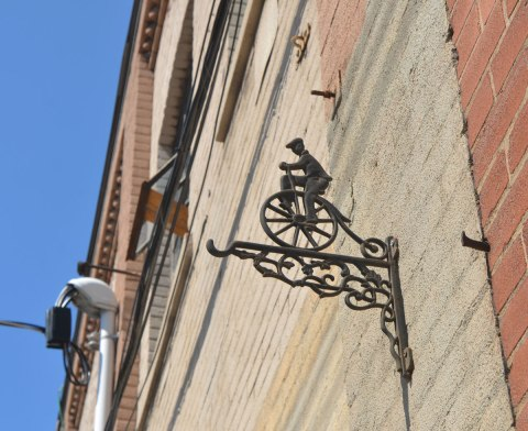 a decorative ornament hanging high on a brick wall, a hook that extends from the wall about 8 to 10 inches, on top is a flat rendition of a boy on an old fashioned bicycle