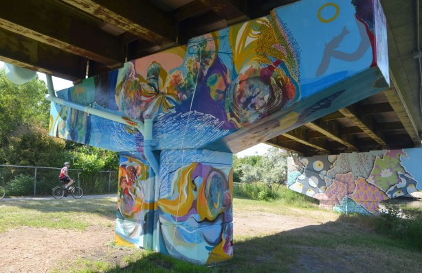 A swirl of colours makes a mural of faces and hands and watery things, on a bent under the Don Valley Parkway