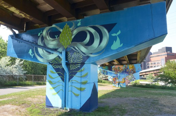 concrete support, or bent, under a ramp has been painted with a mural based on a large dark blue triangle