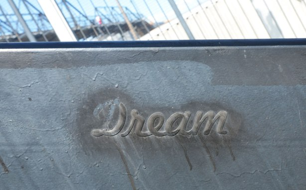 a raised word, 'dream' in cursive that has been stuck on the side of a set of stairs and then painted black to match the steps