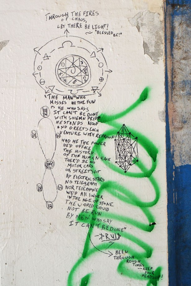 many words written on the wall of an underpass, along with some line drawings. by druid,