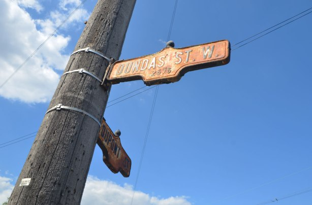 two old Toronto street signs, slightly rusted, on a hydro pole, one for Dundas St. WEst and one for Dupont street