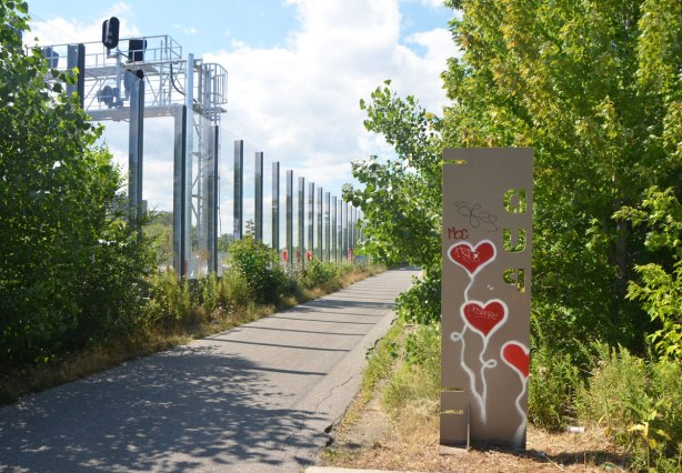 glass fence beside railway tracks, path, trees, also a metal sign on which three red hearts on white stems have been painted.