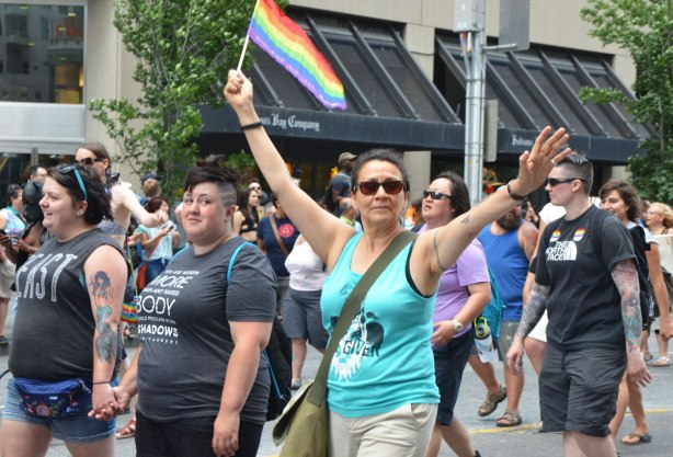 walkers in a dyke march in Toronto - a woman in a turquoise top with her arms raised, a rainbow flag in one had, another woman is grinning