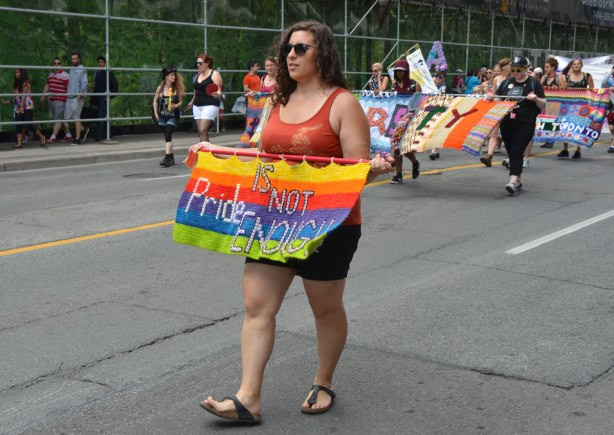 a woman is carrying a crocheted rainbow banner for a dyke march, behind her a larger group is carrying a crocheted banner that says diversity
