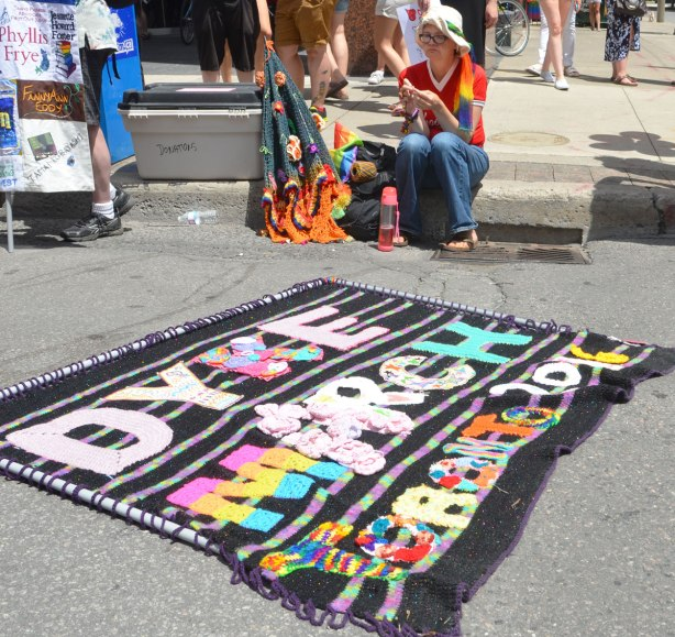 crocheted banner for dyke march is lying on the pavement. A woman is sitting on the kerb and she is crocheting