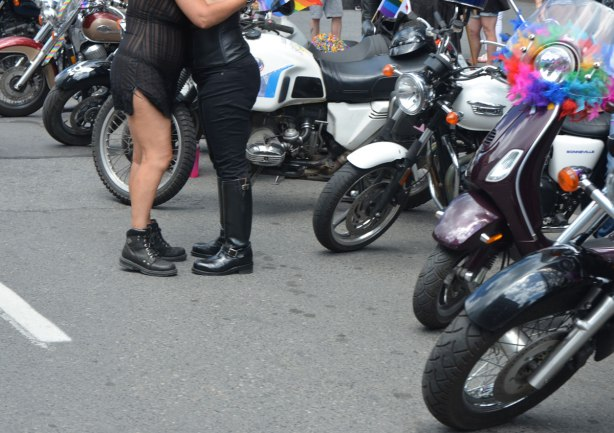 two people hugging, one in black pants and knee high boots, motorcycles parked around them.