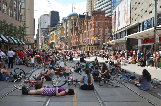 walkers in a dyke march in Toronto - Dykes on bikes, parade has stopped so the cyclists have put down their bikes and many of them are lying down, crowds on the sidewalks watching the parade