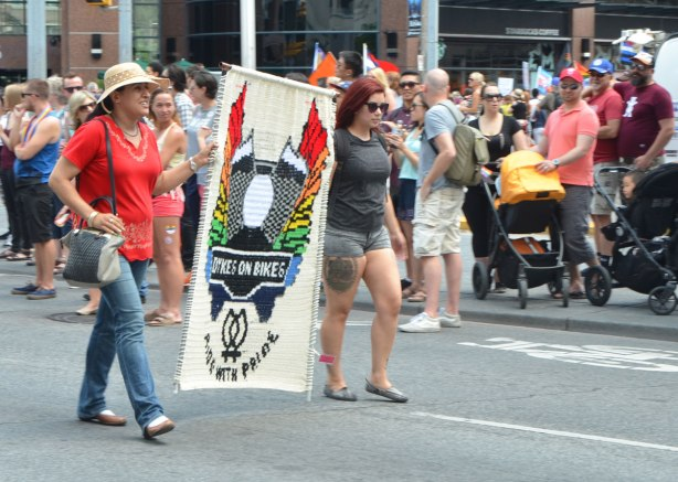 two women carrying a crocheted banner for Dykes on Bikes, walkers in a dyke march in Toronto