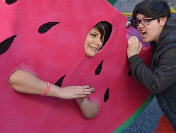 a woman attempts to take a bite out of another woman who is wearing a giant watermelon costume