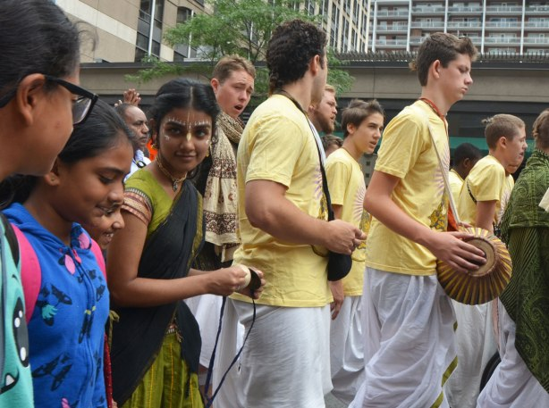a group of young South Asian women walking in a parade. One of them has her face decorated with paint. In front of them is a group of young men in yellow tops and white bottoms, one has a drum.
