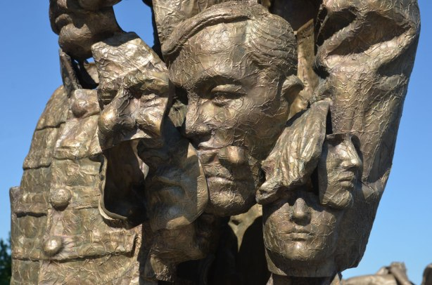 part of a public art installation outdoors created by piecing together fragments of other statues cast in bronze