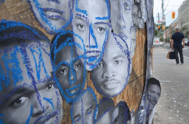 pictures of the faces of black men attached to wood construction hoardings and rough outlines and highlights drawn on the faces with crayon, in red, blue, yellow and green. The faces all look like they are looking into the camera