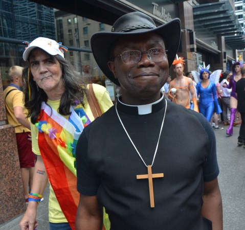 A minister in black shirt and white collar, also wearing a large wood cross on a necklace. Other people dressed for the pride parade are in the background.