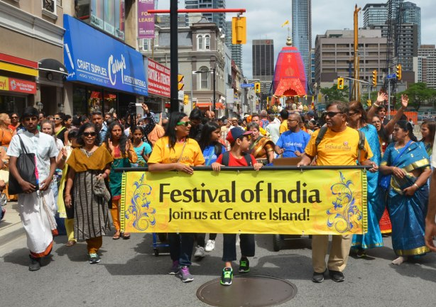 people walk behind a yellow horizontal banner that reads Festival of India, Join us at Centre Island.