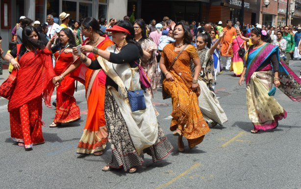 South Asian, Indian, women, in long colourful sarees dancing as they move down Yonge Street in a parade