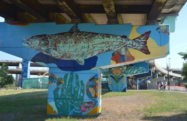 A very large fish is painted across the top of a bent, and a hand is on the vertical part, with finger tips pointed upwards.