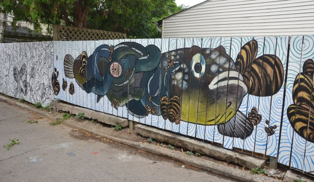 fish mural on a white wood fence, muted tones of greens, blues and browns.