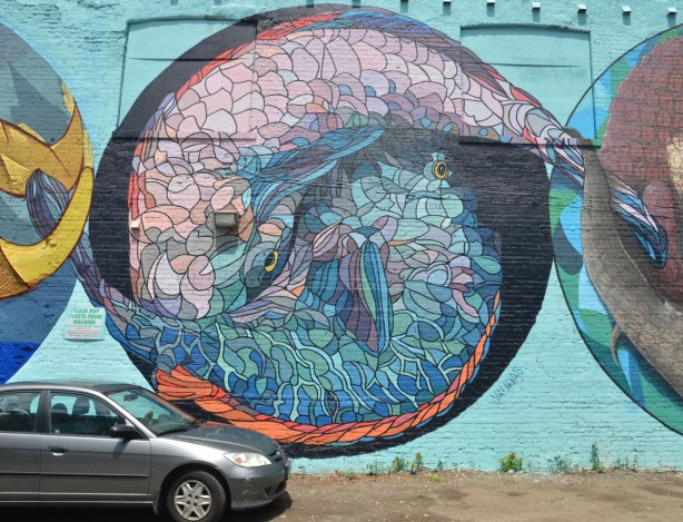 large round mural of two large fish, intricate patterns on the fish, entwined head to tail to form a circle with their bodies