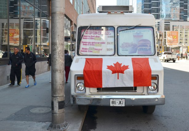 Canadian flag draped over the front of a food truck parked at the side of a street in downtown Toronto