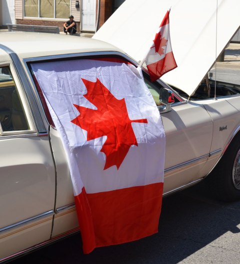 Canadian flag draped over the side of an old car