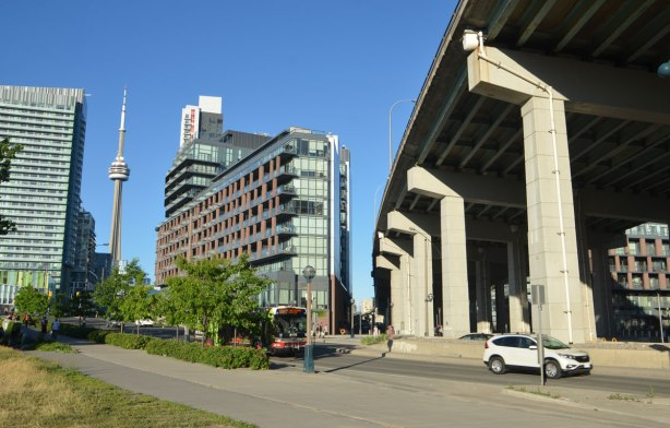 fort york blvd is in the foreground, a TTC bus and a car are on it, the Gardiner is to the right and a short condo building is in the background along with the CN tower