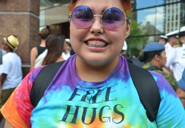 A young person with very short hair, wearing round purple and pink sunglasses and a tie dyed T-shirt that says Free Hugs on it.
