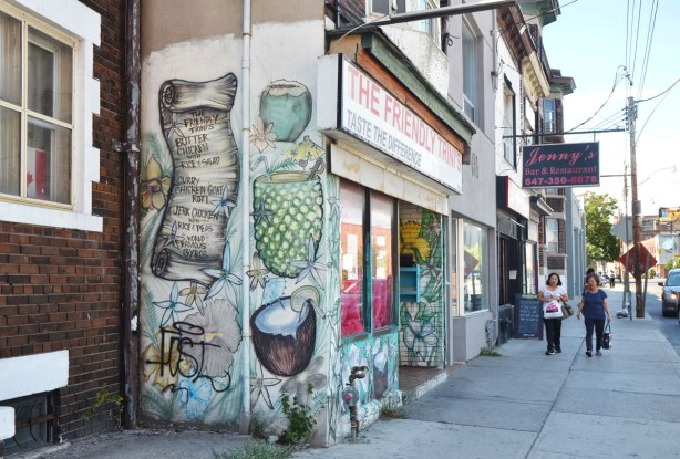 a mural on the side of the Friendly Trinis restaurant that is now closed. Two women are walking on the sidewalk by the restaurant, a sign for Jennys bar and restaurant is in the background. The mural has drinks in coconuts and pineapples as well as a list of some of the food they served