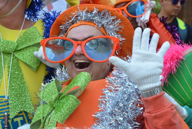 a man dressed as a fruit, an orange, with big green glittery bow in the front and oversized orange frame glasses, also white gloves and an orange hat. He is smiling a big smile and waving at the camera