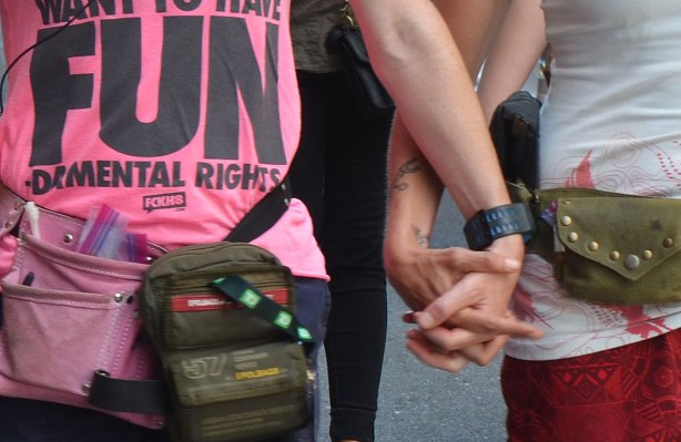 """Two people holding hands, one is wearing a pink T shirt that says """"Women want to have FUN - damental rights"""". Closely cropped picture"""