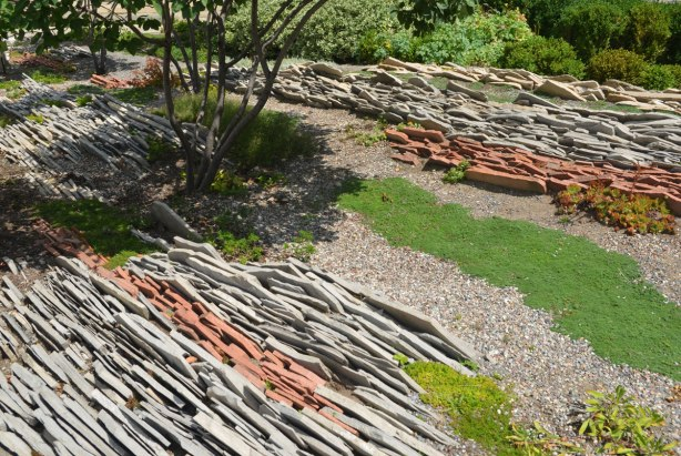 limestone rocks arranged on a slant in a garden, stripes of red rock and grey rock, all just a few inches off the ground