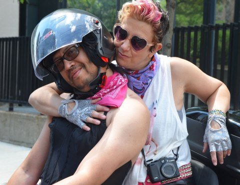 two people on a motorcycle posing for the camera
