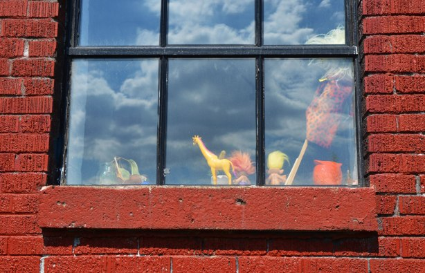 looking into a window, toy yellow giraffe on the window sill as well as two toy trolls, one with yellow hair and the other with orange. Reflections of clouds in the window