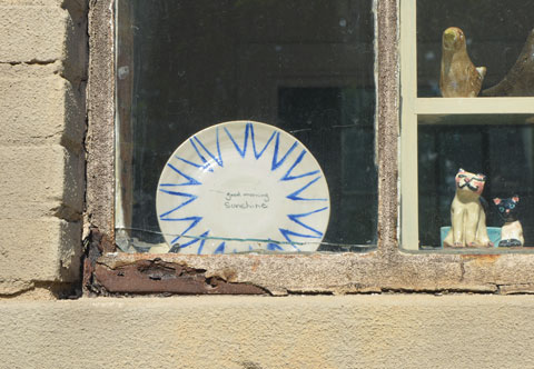 a plate in a window that says Good Morning Sunshine, also two small ceramic figures of cats, and one ceramic dog