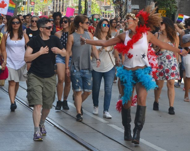 walkers in a dyke march in Toronto - a woman with a red boa is dancing and talking to other women at the same time